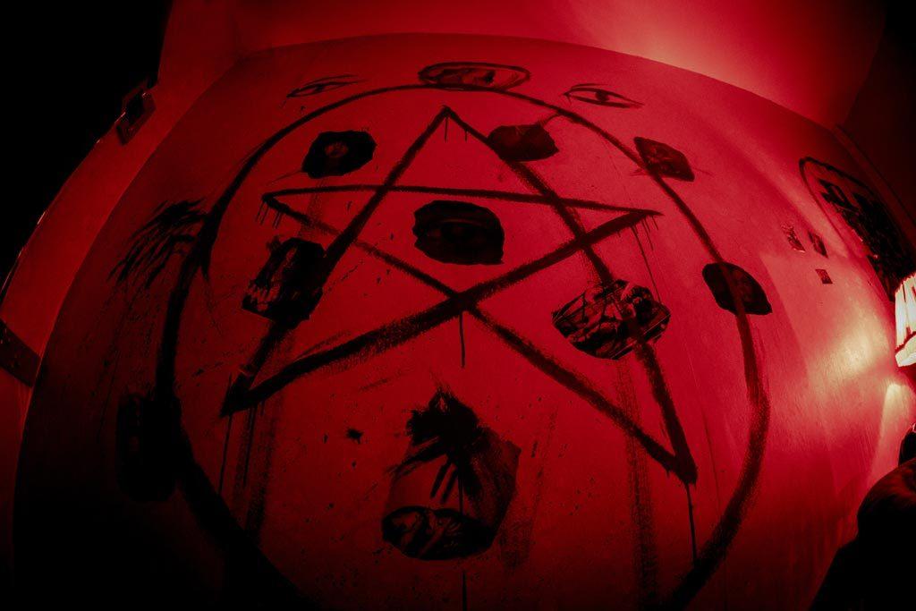 Πεντάλφα ζωγραφισμένη σε κόκκινο τοίχο στο The Ritual Nightmare Edition Escape Room