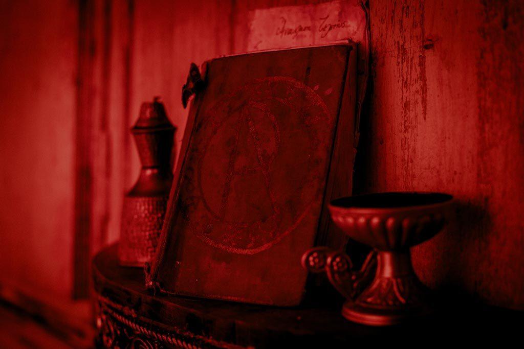 Βιβλίο σε κόκκινο τρομακτικό φωτισμό στο The Ritual Nightmare Edition